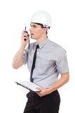 Coordenador com prancheta usando o Walkietalkie Imagem de Stock