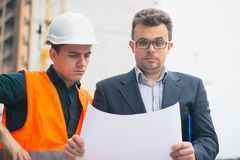 Coordenador confuso com um chefe que trabalha no plano arquitetónico, esboçando um projeto imagens de stock