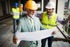 Coordenador, contramestre e trabalhador discutindo no local da construção civil imagens de stock royalty free