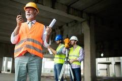 Coordenador, contramestre e trabalhador discutindo no local da construção civil imagem de stock royalty free