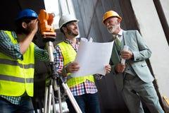 Coordenador, contramestre e trabalhador discutindo no local da construção civil imagens de stock