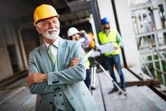 Coordenador, contramestre e trabalhador discutindo no local da constru??o civil imagens de stock