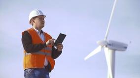 Coordenador da energia do moinho de vento a trabalhar com a tabuleta no por do sol ambiental filme