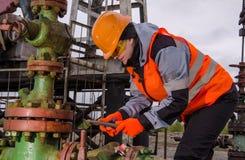 Coordenador da mulher no campo petrolífero que repara a fonte Fotografia de Stock