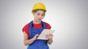 Coordenador da mulher que verifica o plano de construção no touchpad e que olha os objetos, construções em torno dela no fundo do filme