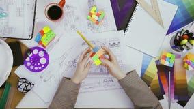 Coordenador da vista superior que trabalha em um esboço do projeto do carro e que joga com o cubo de 2x2 Rubiks filme