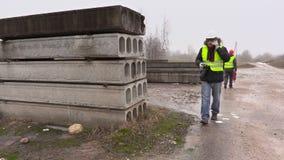 Coordenador de construção com a câmera profissional da foto que fala no telefone celular video estoque