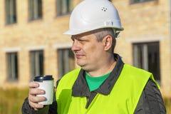 Coordenador de construção com a xícara de café perto da construção fotografia de stock
