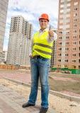 Coordenador de construção de sorriso que levanta no terreno de construção com polegar Fotografia de Stock Royalty Free