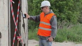 Coordenador de construção perto da construção filmada com PC da tabuleta filme