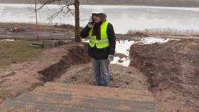 Coordenador de construção que fala no telefone esperto perto do pavimento inacabado filme