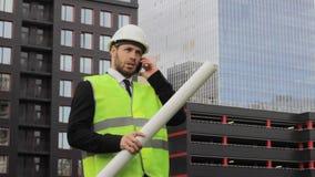 Coordenador do construtor que fala no trabalhador sério do homem de negócios do telefone filme