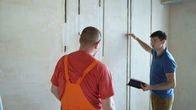 Coordenador e arquiteto que discutem sobre a tabuleta sem fio digital que trabalha no terreno de construção interno filme