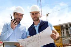 Coordenador e trabalhador que verificam o plano no canteiro de obras Imagens de Stock