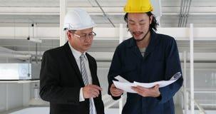 Coordenador executivo asiático e coordenador novo para discutir sobre o modelo na fábrica industrial, video estoque