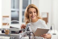 Coordenador fêmea alegre que programa a impressora 3D com tabuleta Fotos de Stock