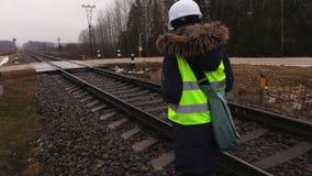 Coordenador fêmea da estrada de ferro para tomar imagens dos trilhos antes da manutenção vídeos de arquivo