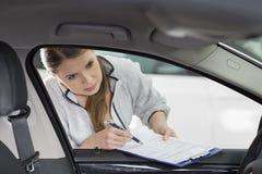 Coordenador fêmea da manutenção com interior do carro de exame da prancheta na oficina Fotografia de Stock Royalty Free
