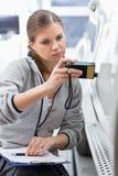 Coordenador fêmea da manutenção que verifica a pintura do carro com o equipamento na oficina Fotos de Stock Royalty Free