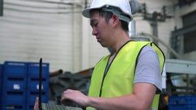 Coordenador industrial com funcionamento do capacete de segurança com o portátil na fábrica filme