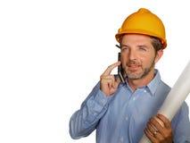 Coordenador industrial ou arquiteto atrativo e bem sucedido no capacete do construtor da segurança que verificam o modelo do proj imagens de stock
