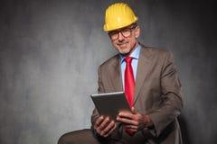 Coordenador maduro em vidros e no capacete vestindo do terno Fotografia de Stock Royalty Free