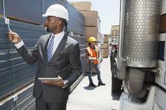 Coordenador masculino afro-americano que inspeciona pranchas quando trabalhador fêmea que está pelo caminhão do leito Imagens de Stock Royalty Free