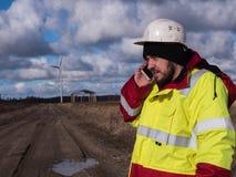 Coordenador masculino no capacete branco que fala pelo telefone moderno no campo com os planos que constroem windmils Imagens de Stock Royalty Free