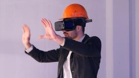Coordenador masculino no capacete de segurança com vidros de VR que projeta o projeto de construção Fotografia de Stock Royalty Free