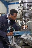 Coordenador masculino Working On Drill do aprendiz na fábrica imagem de stock