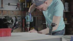Coordenador mestre da habilidade do retrato centrado sobre o furo de um furo com a ferramenta no fundo de uma oficina pequena com filme