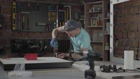 Coordenador mestre novo centrado sobre o furo de um furo com a ferramenta no fundo de uma oficina pequena com instrumentos video estoque