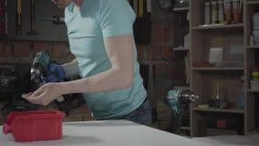 Coordenador mestre profissional do retrato centrado sobre o furo de um furo com a ferramenta no fundo de uma oficina pequena com video estoque