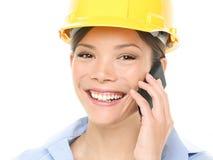 Coordenador - mulher com o capacete de segurança no telemóvel fotografia de stock royalty free