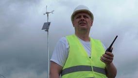 Coordenador no Walkietalkie perto do gerador de vento com painel solar vídeos de arquivo