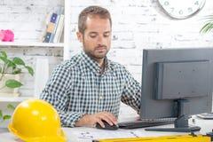 Coordenador novo que trabalha em seu computador fotos de stock