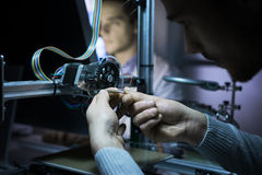 Coordenador novo que trabalha em uma impressora 3D imagem de stock