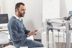 Coordenador novo que trabalha na tabuleta e que verifica a impressora 3D Fotografia de Stock