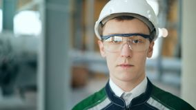 Coordenador novo que veste o capacete protetor que levanta olhando a câmera na fábrica moderna vídeos de arquivo