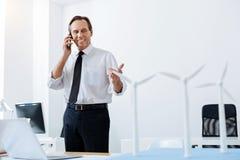Coordenador otimista que discute o projeto novo no telefone Imagens de Stock