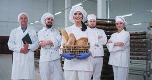 Coordenador principal de vista comercial dos padeiros da equipe da padaria na frente de uma senhora bonita com uma cesta da vista video estoque