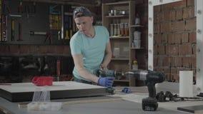 Coordenador profissional do craftman do retrato centrado sobre o furo de um furo com a ferramenta no fundo de uma oficina pequena filme