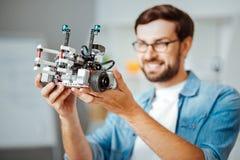 Coordenador profissional positivo que guarda o robô Fotografia de Stock Royalty Free