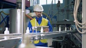 Coordenador profissional que verifica o trabalho do transporte automatizado, máquina da fábrica filme