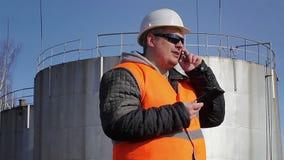 Coordenador que fala no telefone celular perto do tanque de óleo vídeos de arquivo