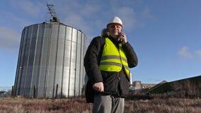 Coordenador que fala no telefone perto do tanque de alumínio video estoque