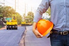 Coordenador que guarda o capacete de segurança no local da construção de estradas imagens de stock