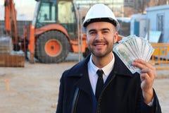 Coordenador que guarda o dinheiro no canteiro de obras imagens de stock