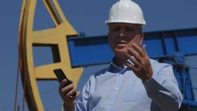 Coordenador Working do petróleo em extrair a indústria petroleira que fala com pilha à disposição fotografia de stock