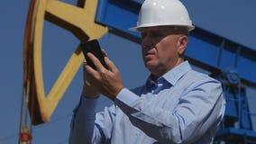 Coordenador Working do petróleo em extrair o texto da indústria petroleira usando o móbil fotos de stock royalty free